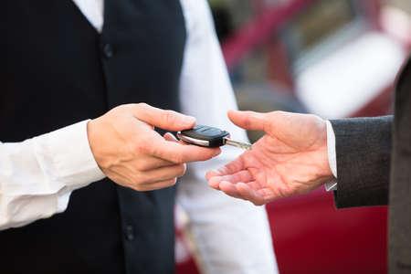 Close-up da mão do manobrista dando chave de carro para o empresário Foto de archivo - 92370045
