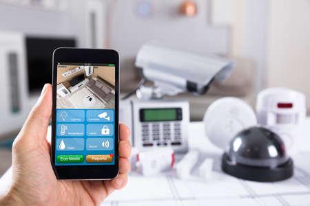 Gros plan de la main d'une personne tenant un téléphone portable avec des images de caméra de vidéosurveillance à l'écran