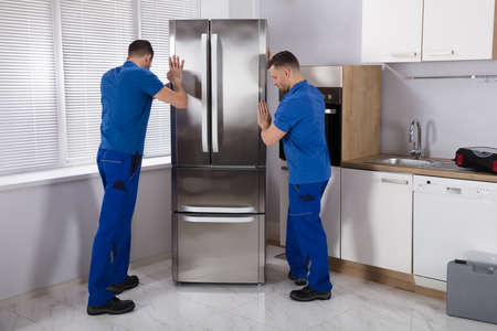 Two Young Male Movers Placing Steel Refrigerator In Kitchen