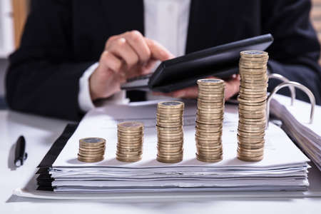 Midsection of businesswoman calculating invoice with stacked coins arranged at office desk