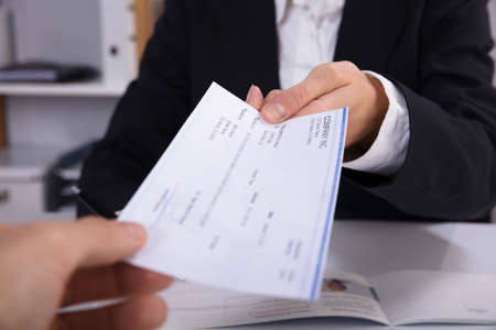 Close-up Of A Business Woman Handing Over Cheque To Her Colleague At Workplace Stok Fotoğraf - 92389718