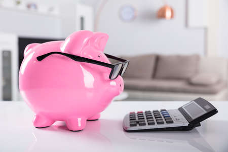 Close-up Of Pink Piggybank Wearing Spectacles With Calculator On Desk Standard-Bild