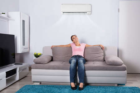 Happy Young Woman Holding Remote Control Relaxing Under The Air Conditioner Stock Photo