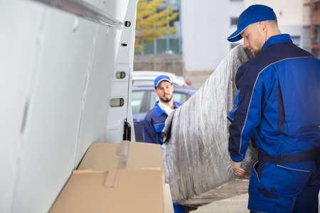 Due motori maschii felici in uniforme che scarica mobilia dal camion