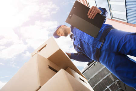 Low Section Of Young Male Worker Standing Near Cardboard Box Holding Clipboard Stock Photo