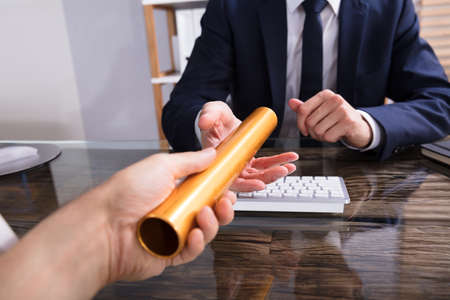 Close-up Of A Person's Hand Passing Golden Relay Baton To Businessperson Archivio Fotografico