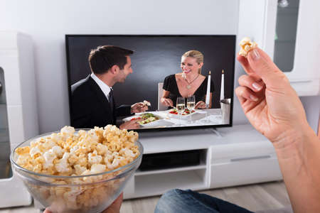 Close-up Of A Person's Hand Holding Popcorn While Movie Plays On Television At Home
