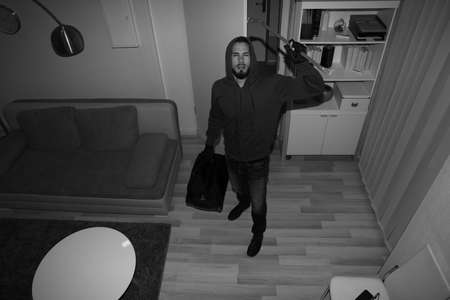 High Angle View Of A Robber Breaking CCTV Camera In Vacant House