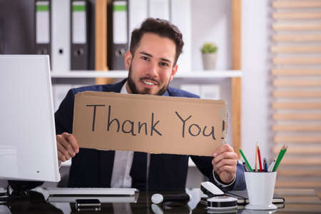 Smiling Young Businessman Holding Cardboard With Thank You Text In Office Stock Photo