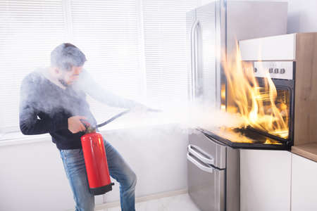 Young Man Using Red Fire Extinguisher To Stop Fire Coming From Oven In Kitchen