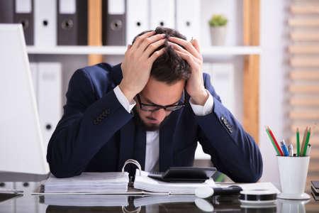 Jonge Mens die aan Hoofdpijn lijden die in Bureau met Bill Over Desk werken