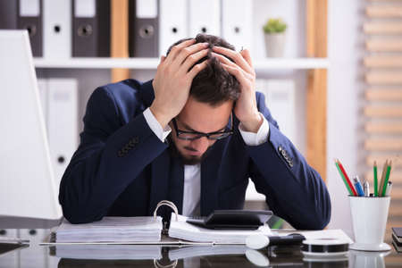 Junger Mann leidet unter Kopfschmerzen arbeiten im Büro mit Rechnung über Schreibtisch Standard-Bild - 92370189
