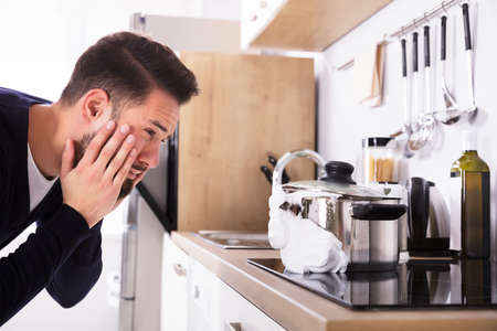 Shocked Young Man Looking At Spilling Out Boiled Milk From Utensil In Kitchen