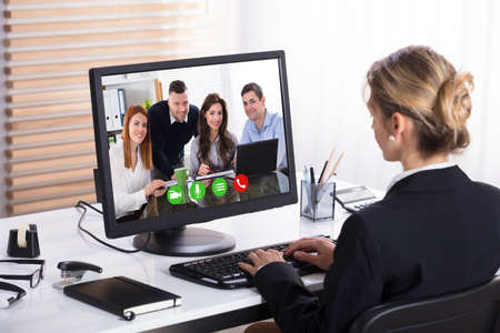 Close-up Of A Businesswoman Video Conference With Her Colleagues On Computer In Office Фото со стока