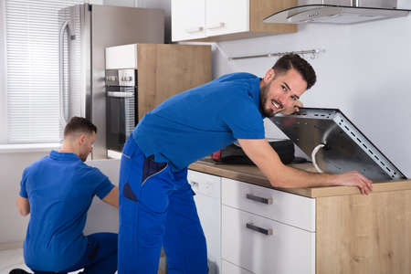 Two Young Men In Blue Uniform Fixing Induction Stove And Sink Pipe In Kitchen Standard-Bild