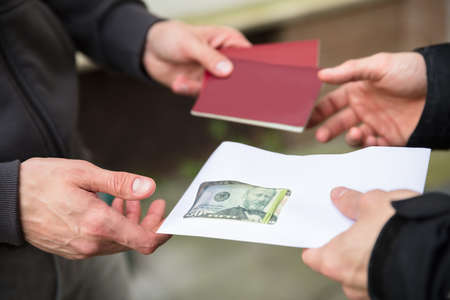 Human Hand Giving Banknote And Buying Illegal Foreign Passport Stock Photo