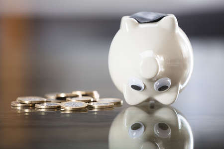 Close-up Of Piggybank Upside Down Near Metallic Coins On Desk