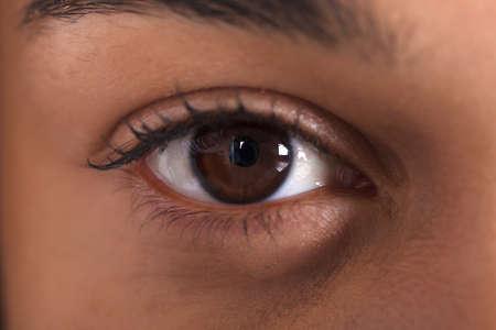 Extremes Nahaufnahmefoto des Auges der afrikanischen Frau