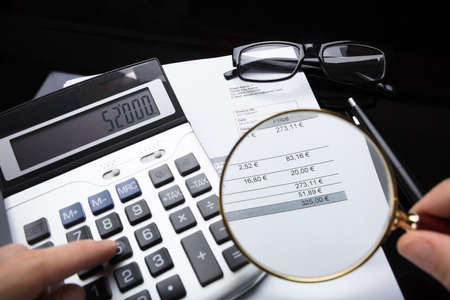 Close-up Of A Businesspersons Hand Analyzing Bill With Magnifying Glass