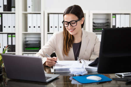 Happy Young Businesswoman Using Calculator At Workplace
