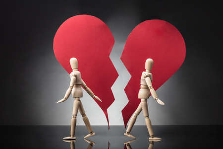 Two Wooden Dummy Standing Against Each Other With Broken Red Heart On Grey Background Stock Photo