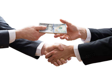 Close-up Of Two Businesspeople Shaking Hands And Receiving Banknote On White Background