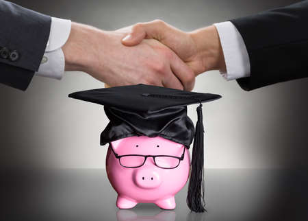 Piggy Bank With Black Graduation Hat And Eyeglasses In Front Of Two People Shaking Hands