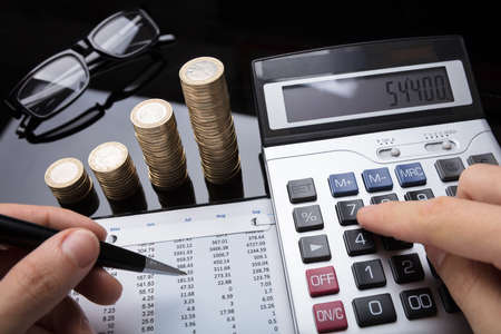 Close-up Of A Businesspersons Hand Calculating Financial Data With Stacked Coins On Desk