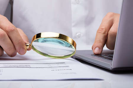 Close-up Of A Businessman Examining Invoice With Magnifying Glass At Desk
