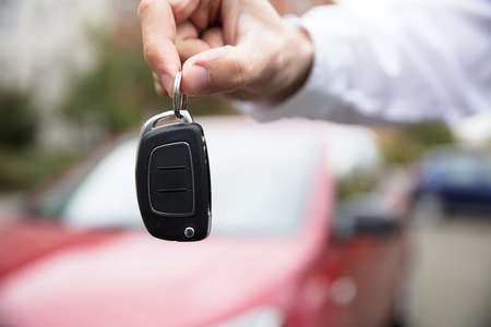 Close-up Of A Persons Hand Holding Car Key Outdoors Standard-Bild