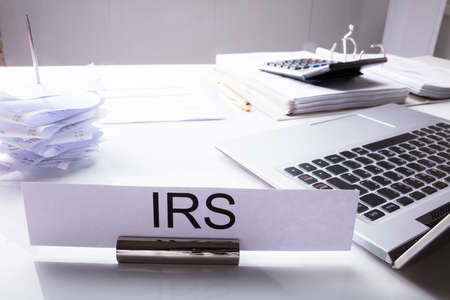 Close-up Of IRS Nameplate On Desk With Laptop And Documents
