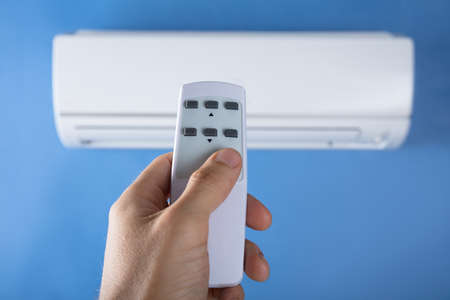 Close-up Of Mans Hand Adjusting Temperature Of Air Conditioner Using Remote