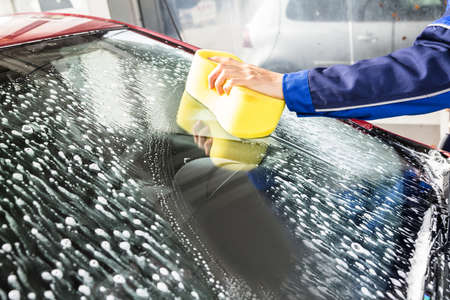 Persons Hand Cleaning Car Windshield With Sponge At Service Station Standard-Bild