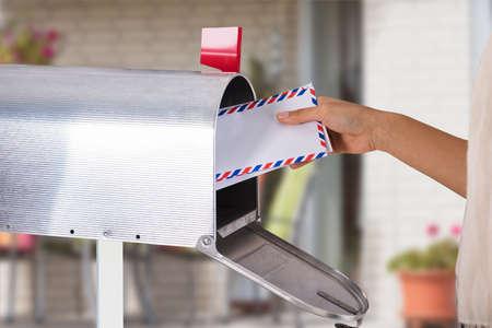Nahaufnahme der Hand einer Person, die Buchstaben vom silbernen Briefkasten entfernt