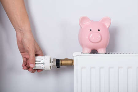 Close-up Of Mans Hand Adjusting Thermostat With Piggy Bank On Radiator Against Wall