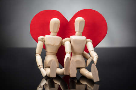 Close-up Of Wooden Dummy Couple Leaning On Red Heart Shape Against Grey Background