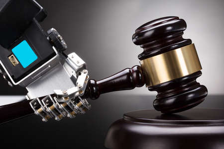 Close-up Of A Robot's Hand Striking Gavel On Sounding Block Against Grey Background Foto de archivo