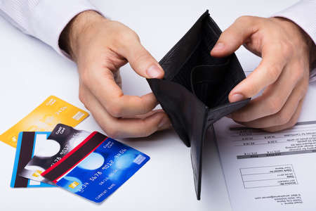 Close-up Of Person Showing Empty Wallet With Credit Card On Desk Standard-Bild