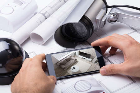 Person Hand Using Home Security System On Mobilephone With On Blueprint With Security Equipment