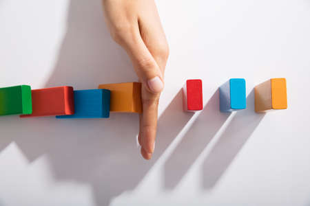 Close-up Of Businessperson Hand Stopping Colorful Blocks From Falling On Table In Office Imagens - 93316291