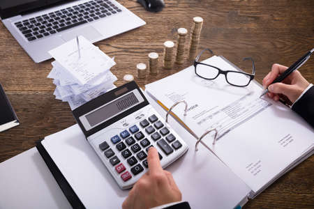 Close-up Of A Businesspersons Hand Calculating Invoice With Calculator In Office