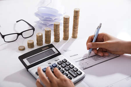 Accountant Calculating Tax Using Calculator On Desk. Save Money Concept