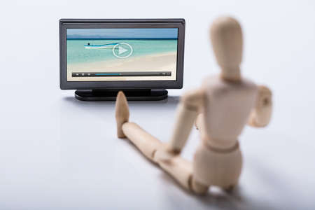 Wooden Figure Holding Remote Watching Video On Television Banque d'images
