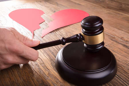 Cropped Image Of Divorce Judge With Broken Heart At Desk Hitting Gavel In Courtroom