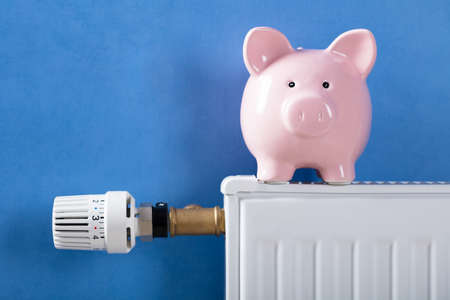 Close-up Of Piggy Bank On Heating Radiator Against Blue Background