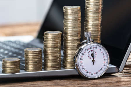Close-up Of Stopwatch With Increasing Stacked Coins On Laptop Standard-Bild