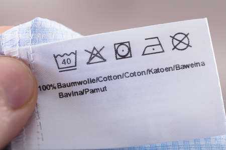 Close-up Of Person Reading Clothing Label Showing Washing Instructions