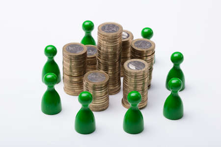Close-up Of Coin Stack Surrounded With Green Figures On White Background