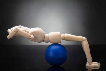 Side View Of A Wooden Dummy Doing Workout On Fitness Ball Against Grey Background