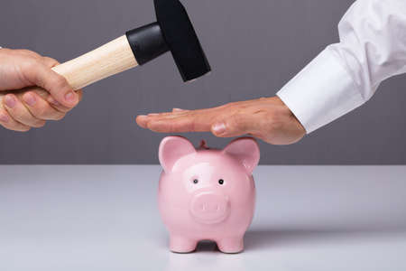 Close-up Of Businessmans Hand Saving Piggybank From Hammering Banque d'images
